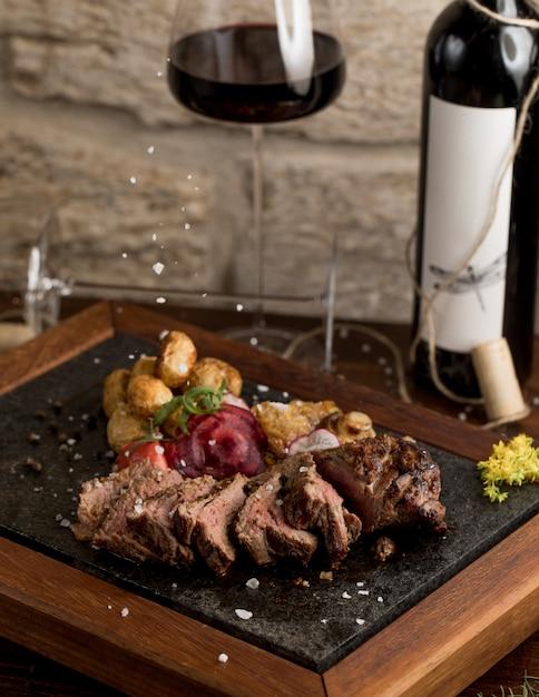 Snijd de biefstuk fijn met gekookte aardappelen en kruiden, en een glas rode wijn Gratis Foto