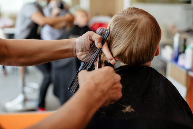 Snijd kapper die kapsel doen aan kleine jongen Premium Foto