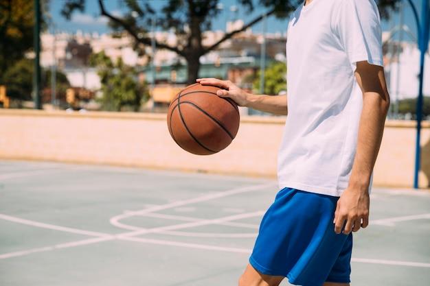 Snijd mannetje in basketbal dat in openlucht vult Gratis Foto