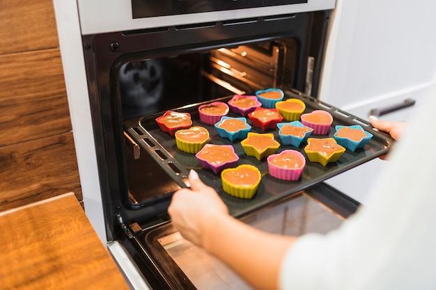 Snijd persoon die cupcakes bakken Gratis Foto