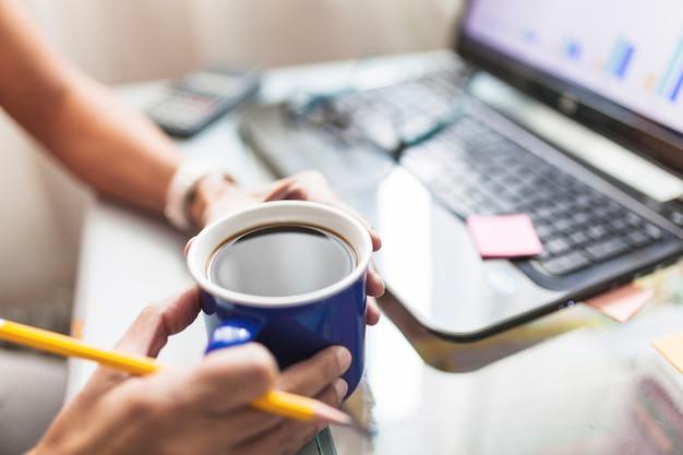 Snijd persoon het drinken van koffie in het kantoor Gratis Foto
