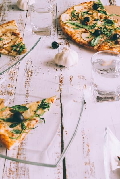 Snijd pizza's op witte tafel Gratis Foto