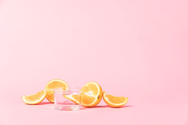 Snijd plakjes oranje fruit op roze achtergrond Gratis Foto