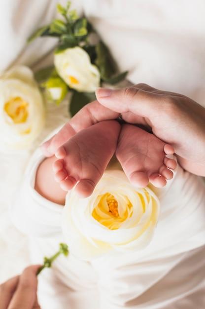 Snijd tedere moeder die babyvoeten houdt Gratis Foto