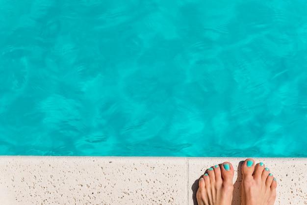 Snijd vrouwelijke voeten bij het zwembad Gratis Foto