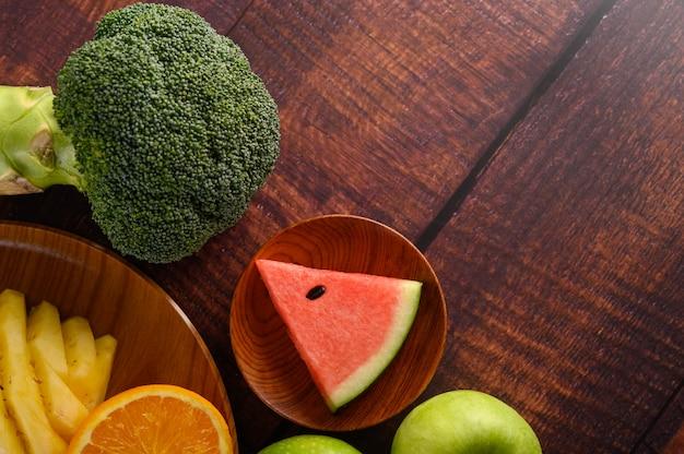 Snijd watermeloenen, sinaasappels en ananas met appels en broccoli op een houten bord. Gratis Foto