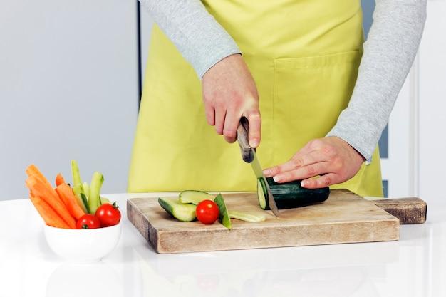 Snijden komkommer en groenten op achtergrond Gratis Foto