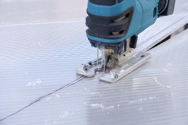 Snijden van polycarbonaatplaat door decoupeerzaag van snijmachine Premium Foto