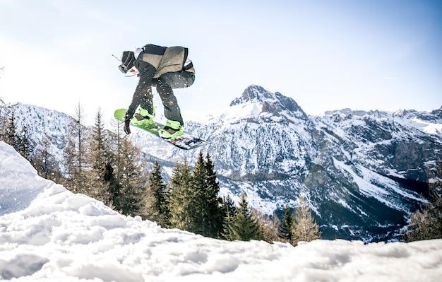 Snoboarder die trucs op de sneeuw uitvoert Premium Foto