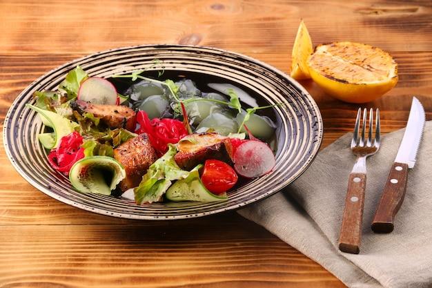 Snoekbaars salade met groenten in plaat op houten tafel citroen voor lunch van vis en bier Premium Foto