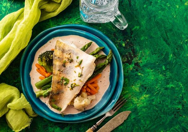 Snoekbaarsfilet met asperges, broccoli en worteltjes. gebakken vis met gestoofde greens Premium Foto