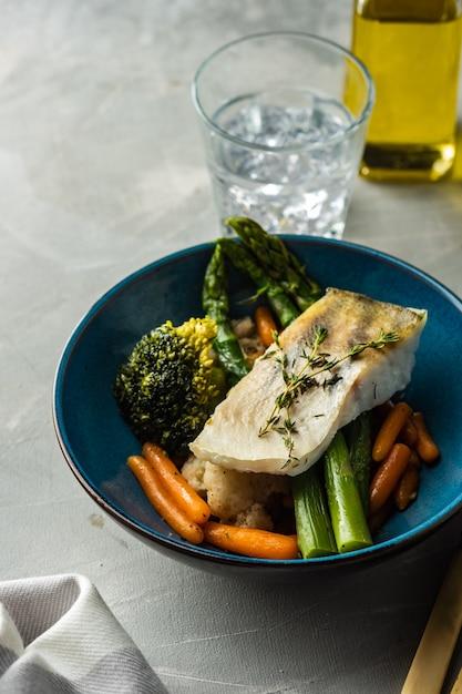 Snoekbaarsfilet met asperges, broccoli en worteltjes. gebakken vis met gestoofde groenten Premium Foto
