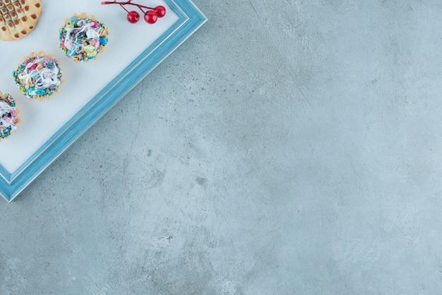 Snoep cupcakes, een koekje en een bessen kerstversiering op een bord op marmeren achtergrond. hoge kwaliteit foto Gratis Foto