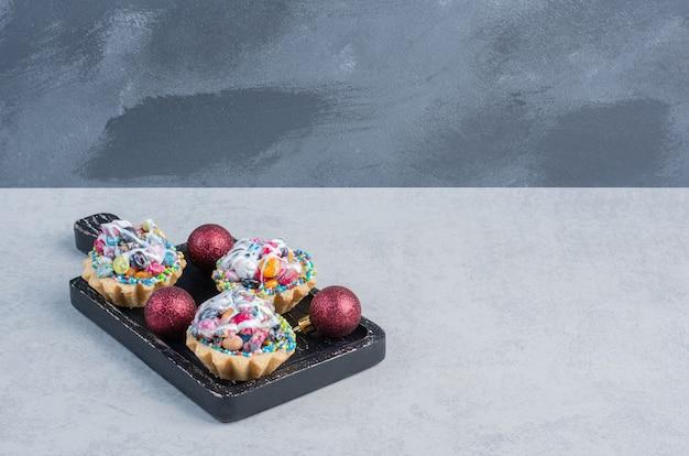 Snoep gegarneerd met cupcakes en kerstballen in een zwarte bak op marmeren oppervlak Gratis Foto