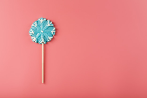 Snoep in de vorm van een blauwe sneeuwvlok op een roze achtergrond. minimalistische platte compositie, vrije ruimte. Premium Foto