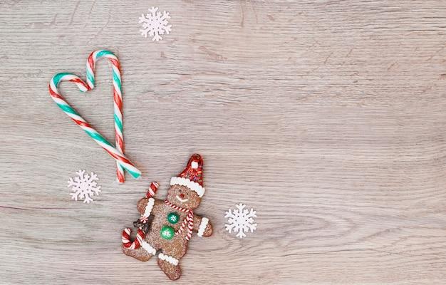 Snoep stokken geplaatst in de vorm van hart in de buurt van cookie sneeuwpop Gratis Foto