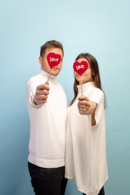 Snoepjes hartvormig. mooi paar verliefd op blauwe studiomuur Gratis Foto