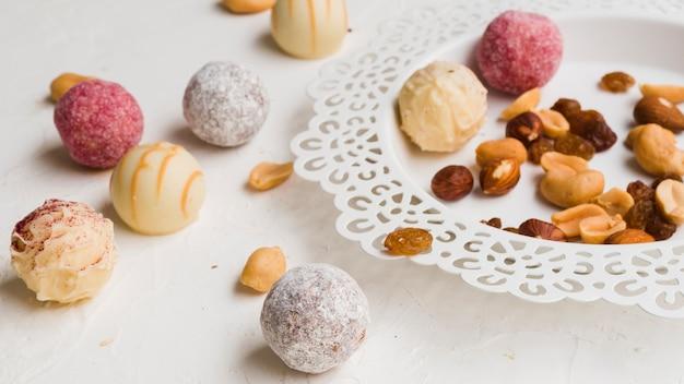 Snoepjes naast plaat op witte achtergrond Gratis Foto