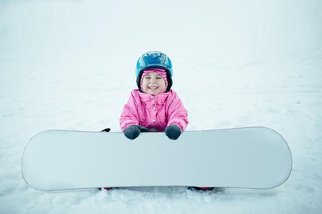 Snowboard wintersport. weinig jong geitjemeisje die met sneeuw spelen die warme de winterkleren dragen. Premium Foto