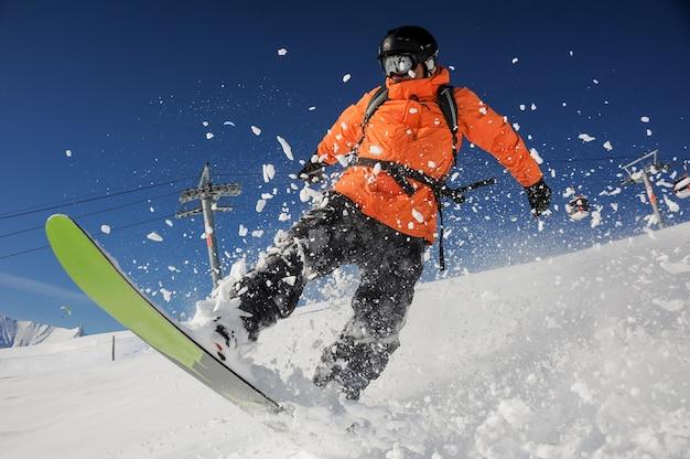 Snowboarder die onderaan de heuvel van de poederberg op zonnige dag berijdt. snowboarden in georgië, goderdzi Premium Foto