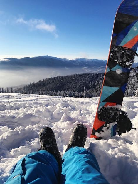 Snowboarder die op a van bergen rust Premium Foto