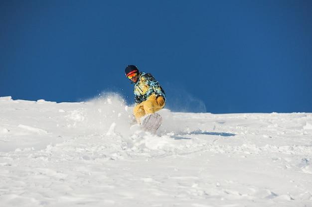 Snowboarder in stijlvolle sportkleding rijden de helling af op zonnige dag in georgië, gudauri Premium Foto