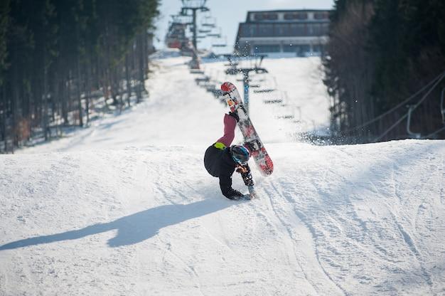 Snowboarder op het moment van vallen op de besneeuwde helling Premium Foto