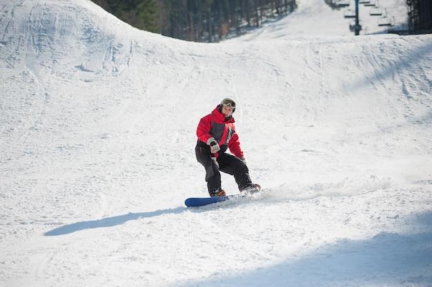 Snowboarder rijdt over verse sneeuw na het springen Premium Foto