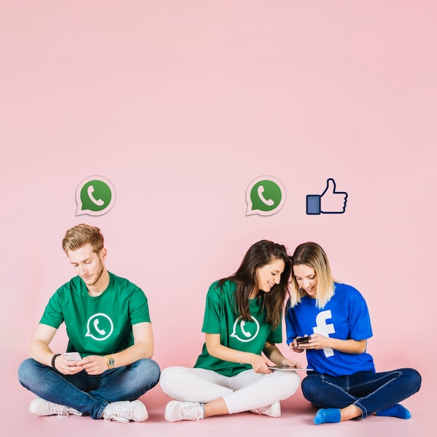 Social media iconen over een groep vrienden met behulp van de mobiele telefoon Gratis Foto