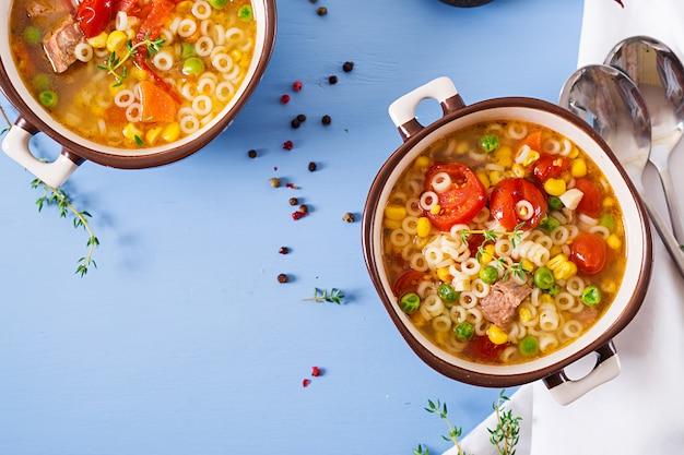 Soep met kleine pasta, groenten en stukjes vlees in kom op blauwe tafel. italiaans eten. bovenaanzicht. plat liggen Gratis Foto