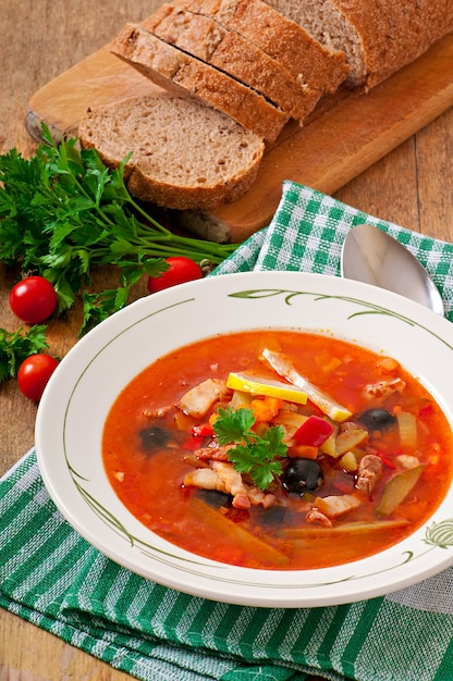 Soep solyanka rus met vlees, olijven en augurken in houten kom Gratis Foto