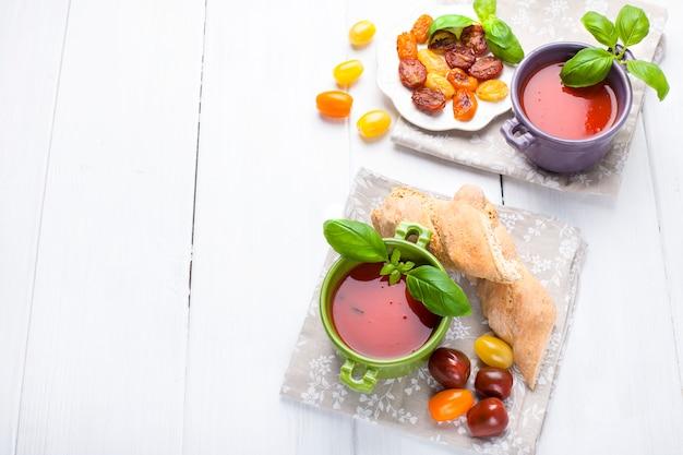 Soepgospacho in heldere kopjes met basilicum op een witte achtergrond Premium Foto