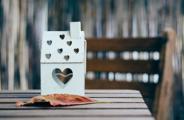 Soft focus shot van een huisvormige lantaarn met hartgaten op een houten tafel Gratis Foto