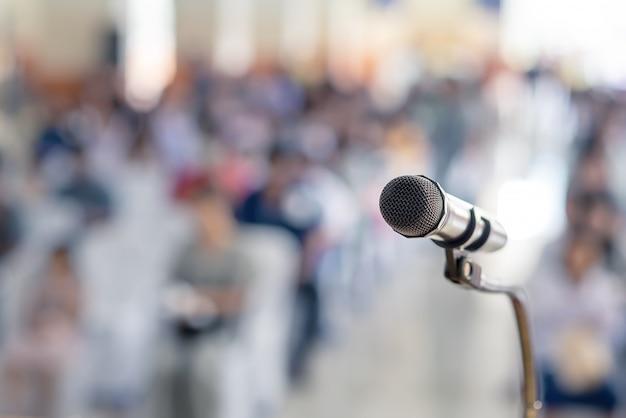 Soft focus van hoofdmicrofoon op het podium van student oudersbijeenkomst op zomerschool of evenement met onscherpe achtergrond, onderwijsvergadering op het podium en kopie ruimte, selectieve focus op hoofdmicrofoon Premium Foto