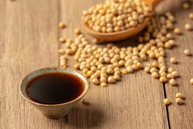 Sojasaus en sojabonen op houten vloer sojasaus voedsel voedingsconcept. Gratis Foto