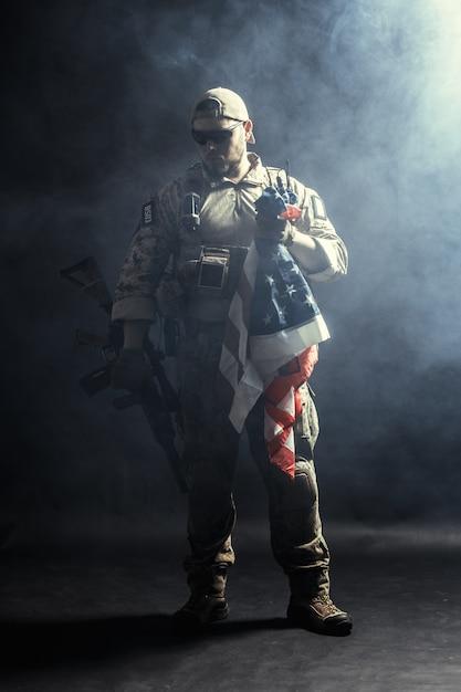 Soldaat bedrijf machinegeweer met nationale vlag Premium Foto