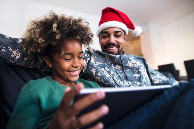 Soldaat in uniform dragen kerstman hoed zitten door zijn dochter op de bank en met behulp van tablet-computer Gratis Foto
