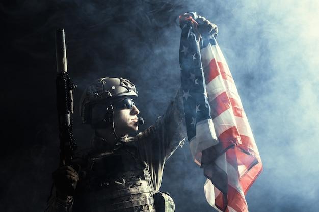 Soldaat machinegeweer met nationale vlag te houden Premium Foto