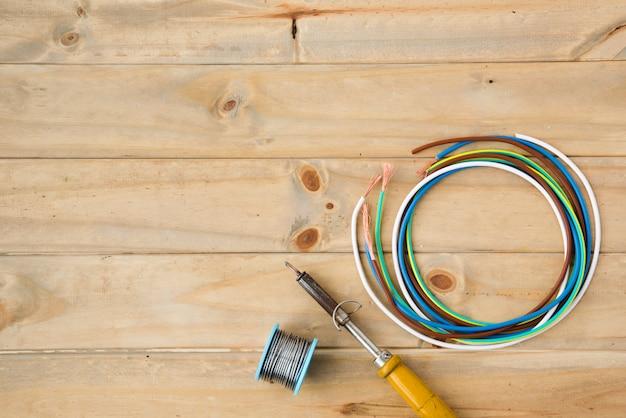 Soldeerbout en soldeerdraad met kleurrijke kabel op houten oppervlak Gratis Foto