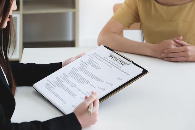 Sollicitatiegesprek in kantoorconcept, focus op cv-papier, werkgever beoordeelt goed cv van voorbereide bekwame sollicitant, recruiter overweegt sollicitatie of hr-manager die een wervingsbeslissing neemt Premium Foto