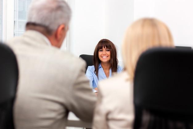 Sollicitatiegesprek tussen een senior koppel en een jonge vrouw Premium Foto