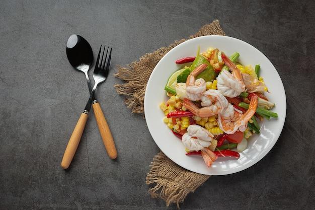 Som tum met maïs en garnalen, geserveerd met rijstnoedels en groene salade versierd met thaise voedselingrediënten. Gratis Foto