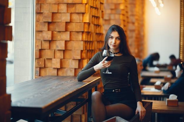 Sommelier die rode wijn proeft. portret van elegante vrouw met rode lippen close-up. dame glas met rode wijn te houden en camera te kijken. Gratis Foto