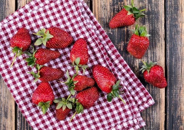 Sommige aardbeien op picknickdoek op houten vlakke lijst, lagen. Gratis Foto