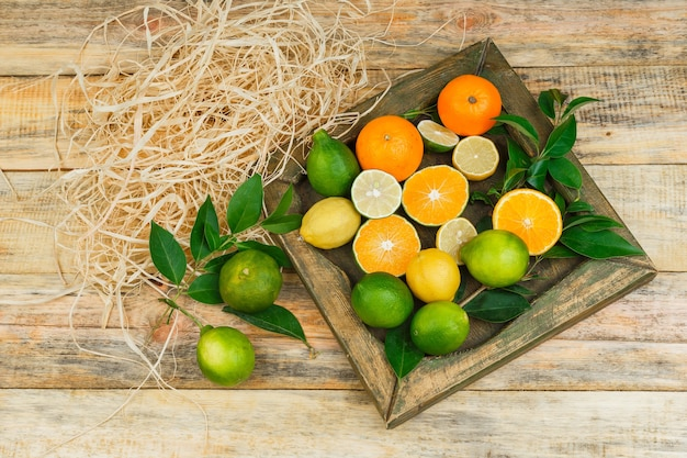 Sommige citrusvruchten in een bronzen plaat op een houten bord Gratis Foto