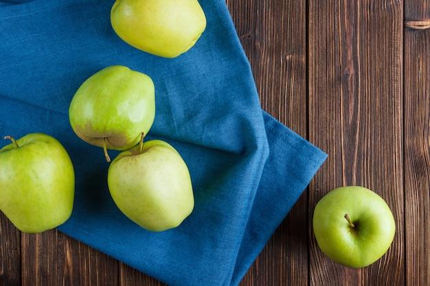 Sommige groene appels op blauwe doek en houten achtergrond, bovenaanzicht. Gratis Foto