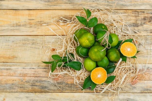 Sommige mandarijnen met bladeren op een houten bord Gratis Foto