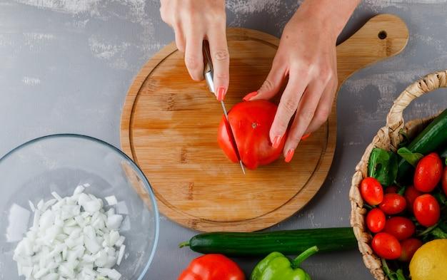 Sommige vrouw snijden tomaat met gehakte uien, groene paprika op een snijplank op grijze ondergrond, bovenaanzicht Gratis Foto