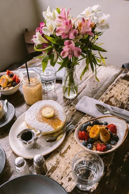 Soorten voedsel, koekjes en drankjes op tafel voor de bloemenvaas Gratis Foto