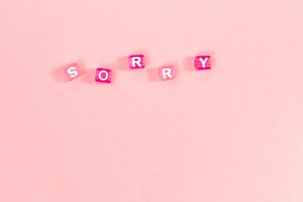 Sorry inscriptie gemaakt van kleurrijke kubus kralen met letters. feestelijk roze concept als achtergrond met exemplaarruimte Premium Foto